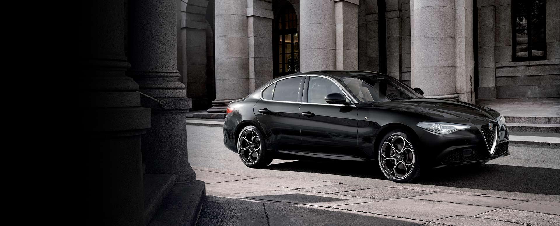Auto sportiva Alfa Romeo Giulia vista laterale su strada colorazione nera
