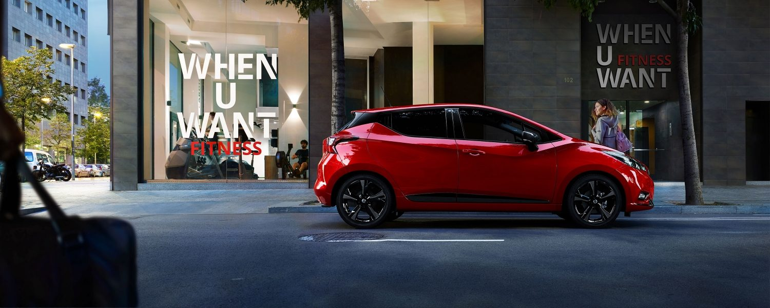 Profile shot of a red, New Nissan N-SPORT driving through the city with When U Want Fitness in the background